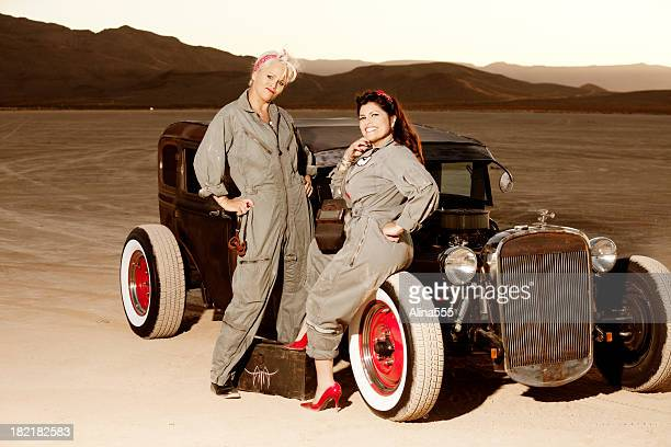 Retro pinup girls in mechanic's coveralls by a classic car