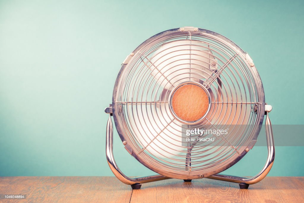 Retro portable office or home cooling fan in working mode standing on table. Vintage instagram style filtered photo : Stock Photo