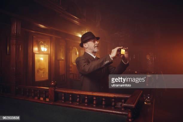 retro pub old-fashioned lifestyle senior men portrait active senior using smartphone - obsoleto foto e immagini stock