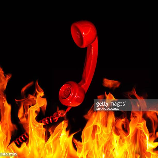 Retro red telephone handset and flames