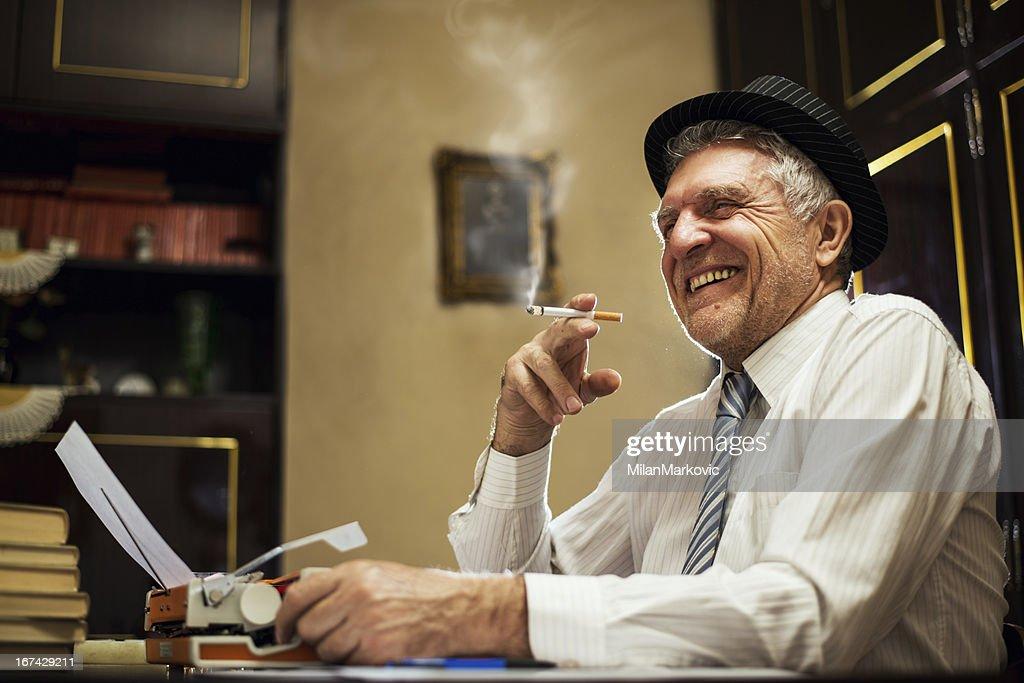 Retro homem idoso com um cigarro Escritor : Foto de stock