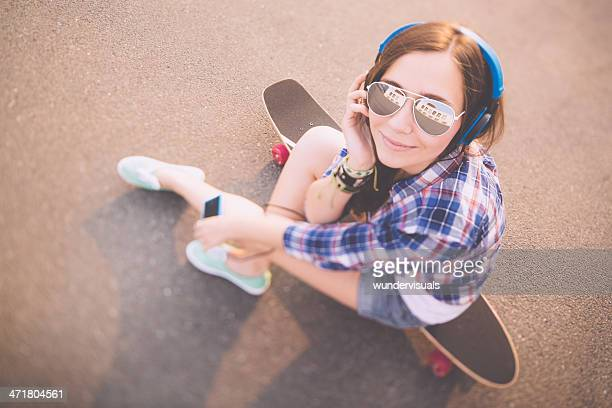 Retro Skater Girl enjoying music on skateboard