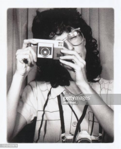 retro style 1980s woman taking photograph with vintage camera - schwarzweiß bild stock-fotos und bilder