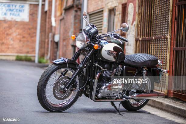 retro style classic motorbike in an alley - triumph motorcycle stock pictures, royalty-free photos & images