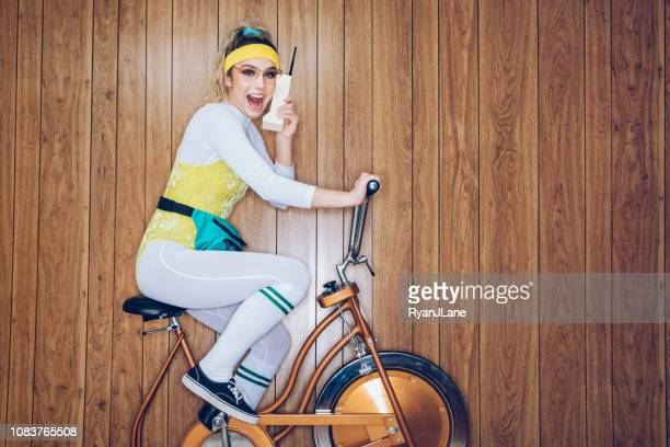 retro style exercise bike woman eighties era brick phone - fashion oddities stock pictures, royalty-free photos & images