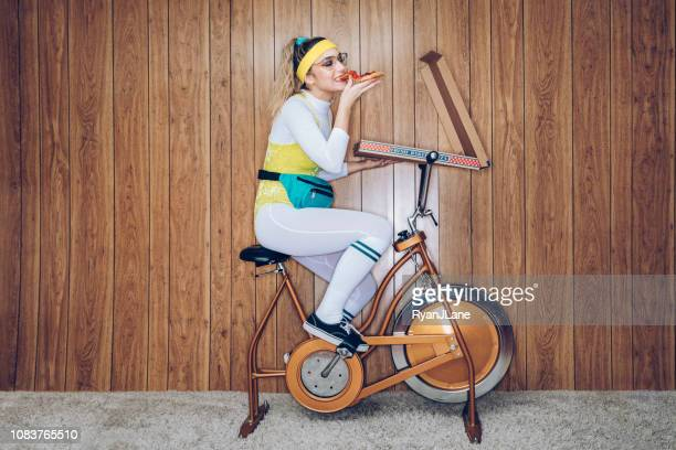 retro style exercise bike woman eighties era eating pizza - man made object stock pictures, royalty-free photos & images
