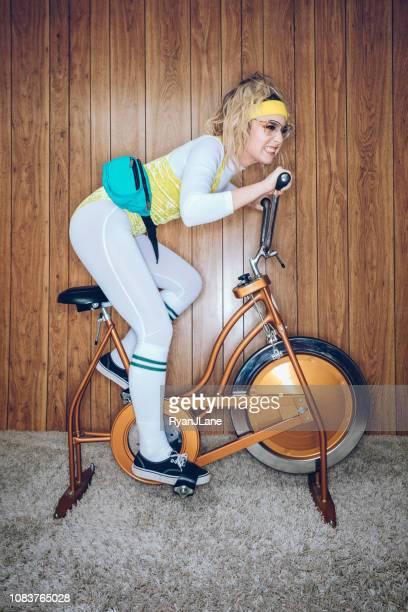 retro style exercise bike woman eighties era - bizarre fashion stock pictures, royalty-free photos & images