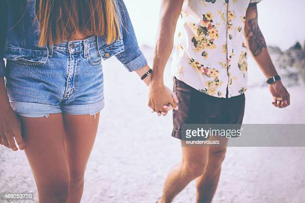 Retro style hipster couple holding hands at the beach