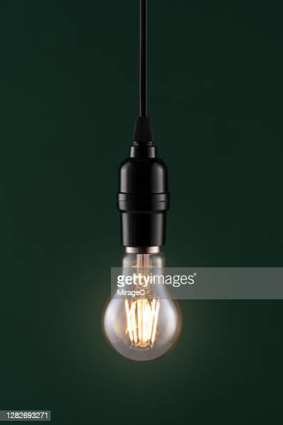 retro style light bulb on dark green - フィラメント ストックフォトと画像