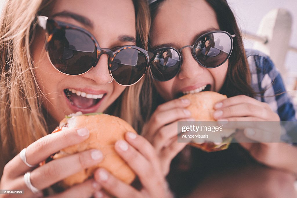 Retro style shot of teenage girl best friends eating burgers : Stock Photo