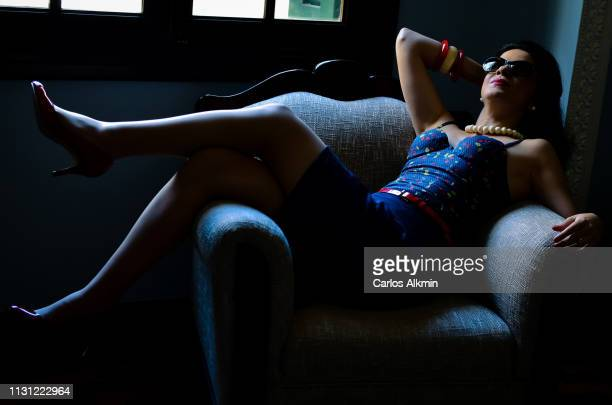 retro style woman with blue dress on sofa - carlos alkmin stock pictures, royalty-free photos & images
