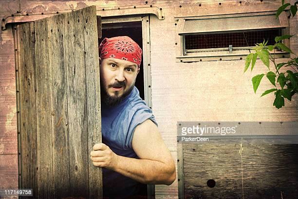 retro styled image of man in old trailer - redneck stock photos and pictures