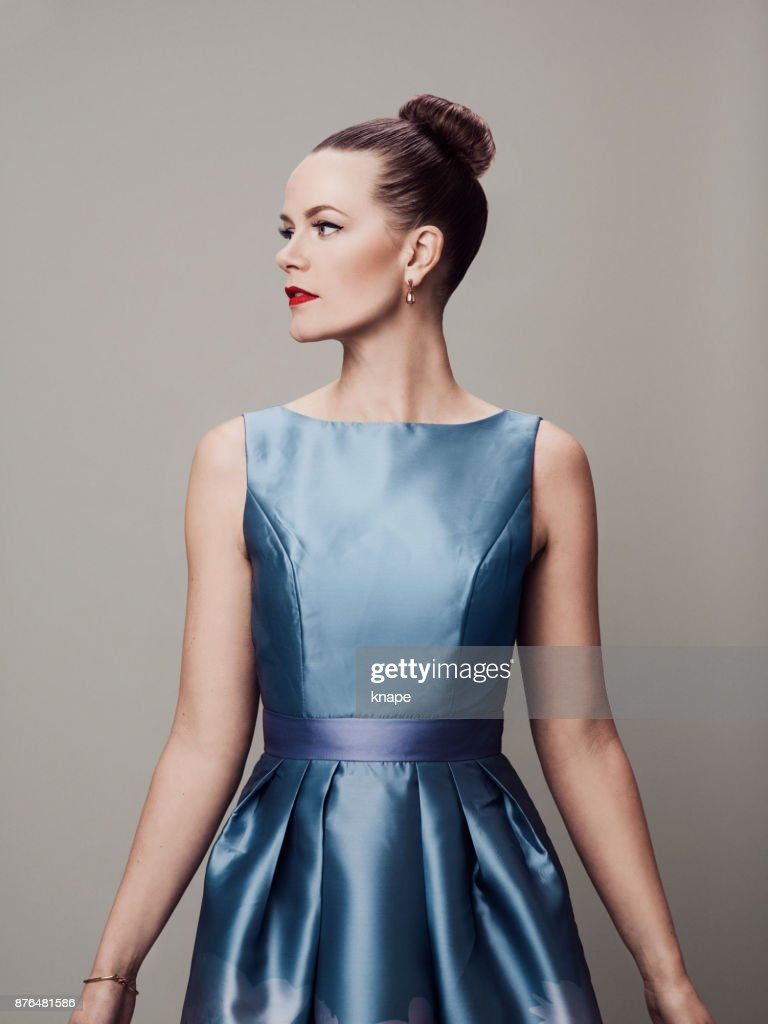 Retro styled woman with make-up red lips and eyeliner in 60s dress : Stock Photo