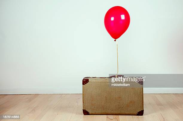 Retro suitcase with red balloon attached stands on the floor