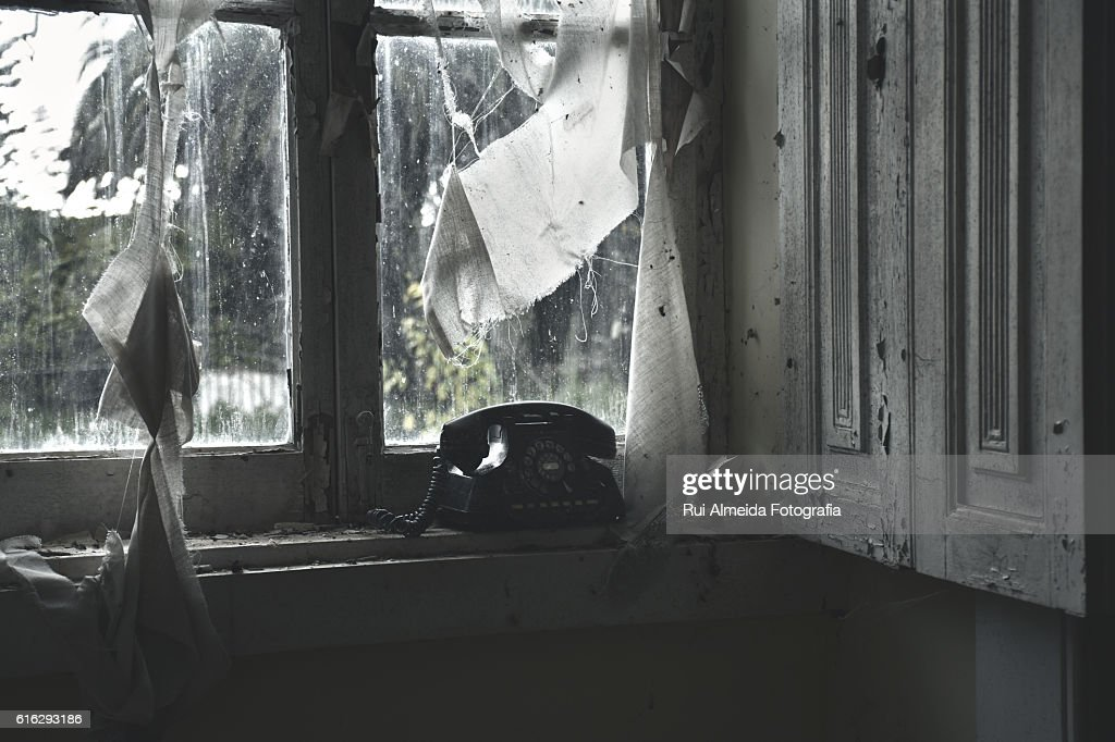 Retro telephone over a dirty window : Stock Photo