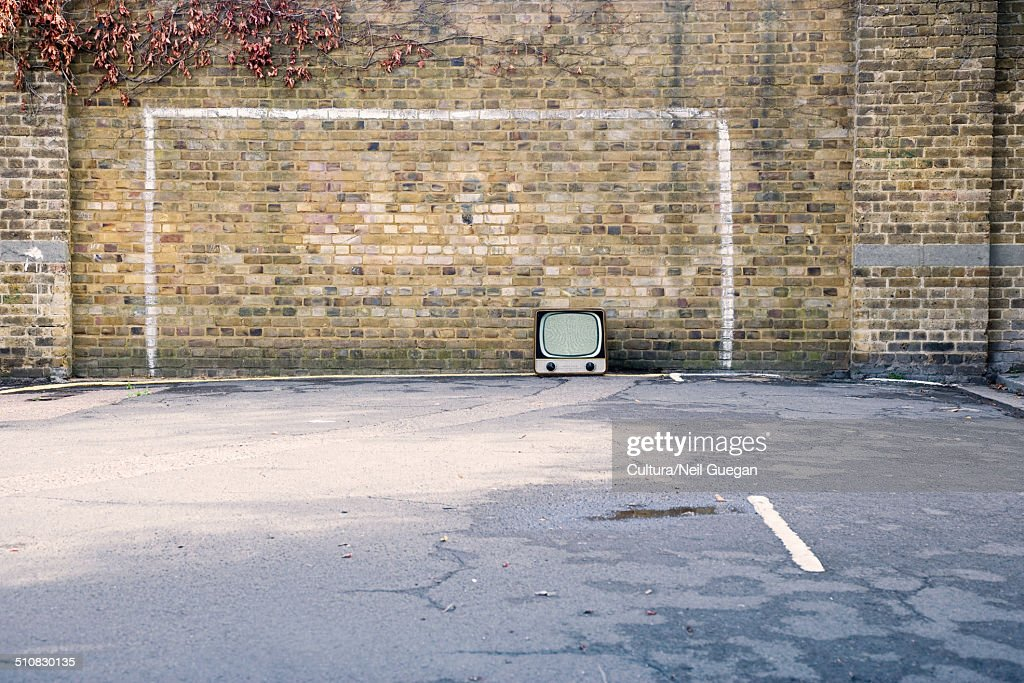 Retro television in football goal painted on brick wall : Stock Photo