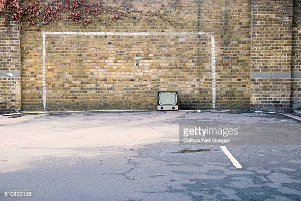 Retro television in football goal painted on brick wall
