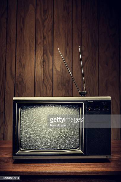 Retro television on wood table with paneled walls