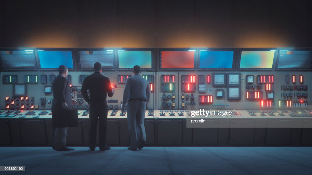 Retro underground control room with men in front of the console : Stock Photo