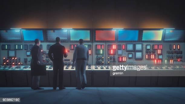 retro underground control room with men in front of the console - atomic imagery stock pictures, royalty-free photos & images