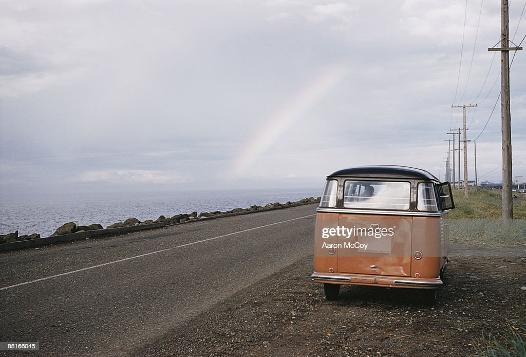 Retro van on side of road with rainbow in horizon : Stock Photo