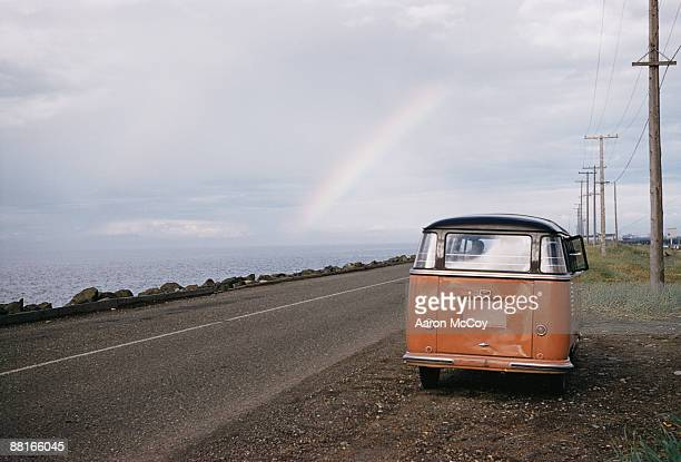 Retro van on side of road with rainbow in horizon