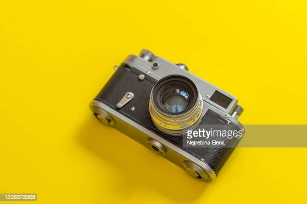 retro, vintage film camera on a yellow colorful fashionable modern background. camera lens with reflections. film camera - body camera stock pictures, royalty-free photos & images