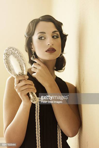 Retro woman adjusting her earring in a hand mirror