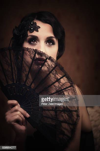 retro woman hiding behind a lace fan