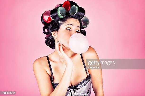 retro woman in curlers blowing bubblegum bubble - krulspelden stockfoto's en -beelden
