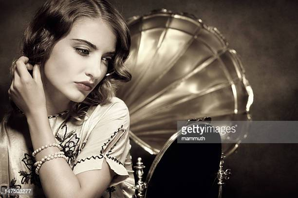 retro woman listening to music and looking in the mirror