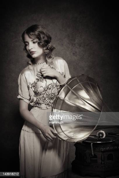 retro woman listening to music on gramophone - picture of phonograph stock photos and pictures