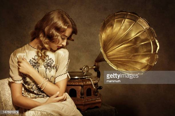 retro woman listening to music on gramophone - gramophone stock pictures, royalty-free photos & images