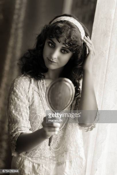 Retro woman looking at herself in a silver hand mirror