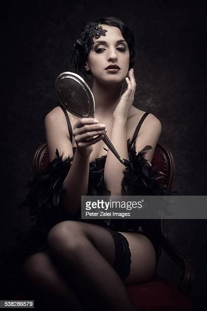 Retro woman looking at herself in a silver mirror