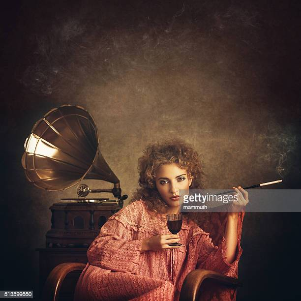 Retro woman smoking and drinking at the gramophone