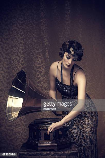 retro woman winding up a gramophone - gramophone stock pictures, royalty-free photos & images