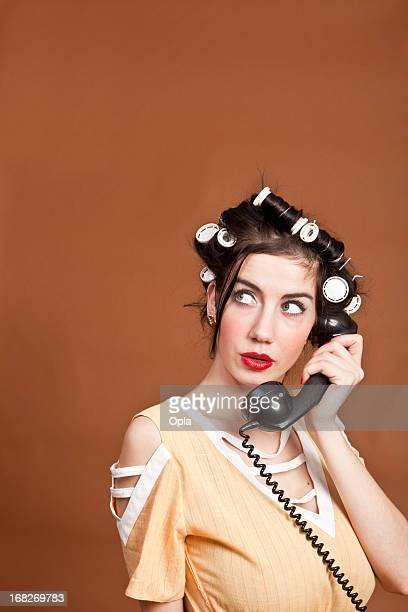 Retro woman with curlers and telephone