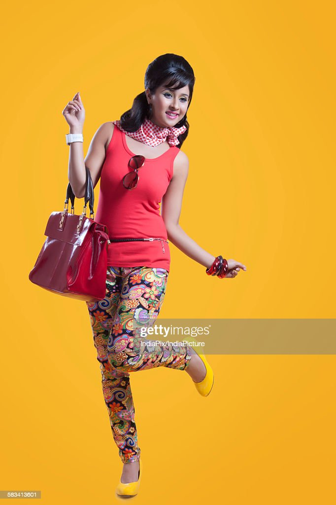Retro woman with hand bag smiling : Stock Photo