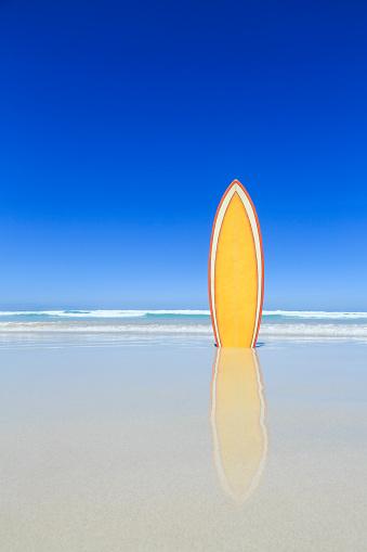Retro yellow surfboard on the beach. - gettyimageskorea