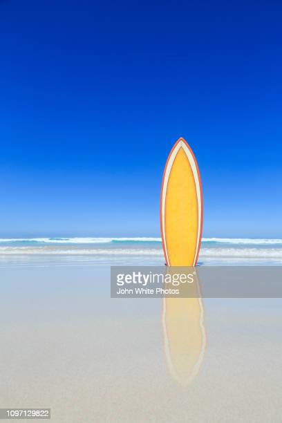 retro yellow surfboard on the beach. - surfboard stock pictures, royalty-free photos & images