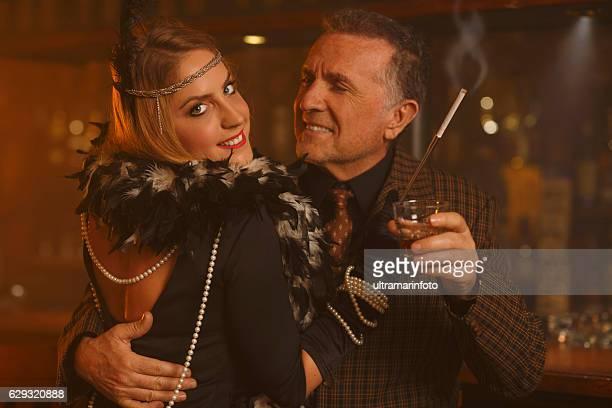 retro  young woman and active stylish senior man drinking whiskey - pareja hombre mayor y mujer joven fotografías e imágenes de stock