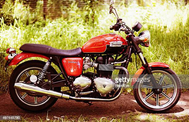 retro-style 2012 triumph bonneville motorbike next to tall grass - triumph motorcycle stock pictures, royalty-free photos & images