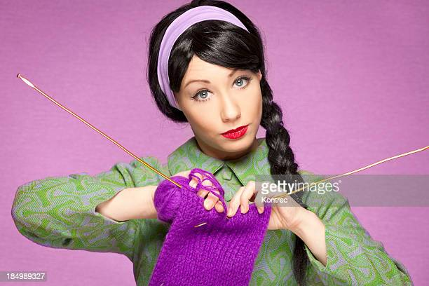 Retro-style woman wearing green, knitting with purple yarn