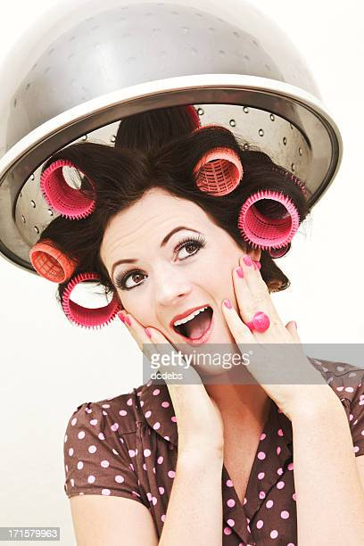 Retro-styled young woman in curlers under salon hairdryer