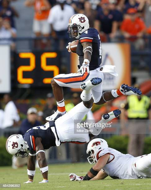 Return man Quan Bray of the Auburn Tigers jumps over teammate Robinson Therezie on a punt return during the game against the Arkansas Razorbacks at...