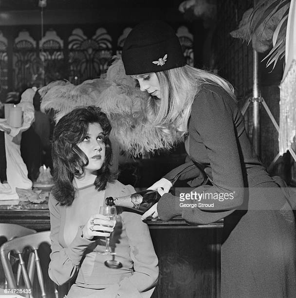 A return to the 1920s look during a champagne tea party at the Biba boutique London UK 25th October 1970 Shop manager Eleanor Powell pours a glass of...