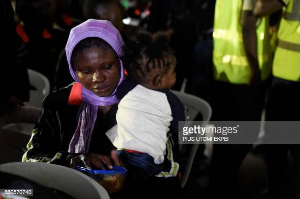 A returnee tries to feed a child after leaving chartered aircraft that brought home 150 migrants from Libya at the Murtala Mohammed International...