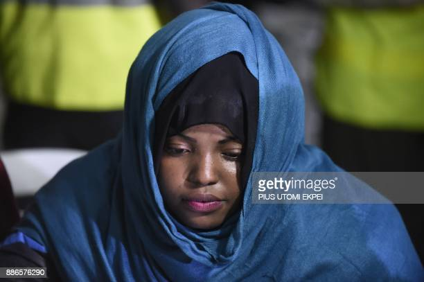 A returnee waits during screening by state officials after arriving in a chartered aircraft that brought home 150 migrants from Libya at the Murtala...