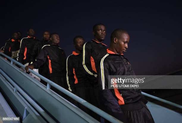 Returnees alight from a chartered aircraft that brought home 150 migrants from Libya at the Murtala Mohammed International Airport in Lagos on...